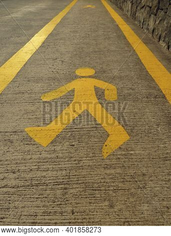 Background Of Yellow Pedestrian Sign On The Walk Way. Close Up Of Pedestrian Walking Figure Painted