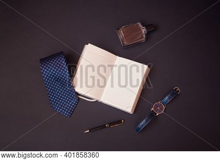 Opened Diary, Stylish Blue Necktie, Perfume, Watch And Black Pen On Dark Background. Top View, Copy