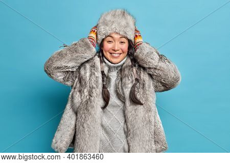 Pleased Young Eskimo Woman Going To Travel On Frozen Lake Smiles Positively Keeps Hands On Hat Wears