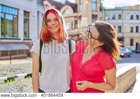 Outdoor Portrait Of Happy Mother And Daughter Of Teenager 16, 17 Years Old Hugging Together. Family,