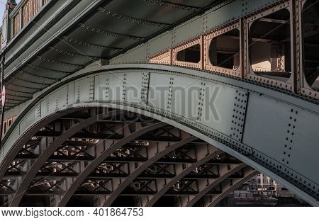 Side View Of Beams And Rivets-structure Under The Bridge Span In The Setting Sun. Large Metal Bridge