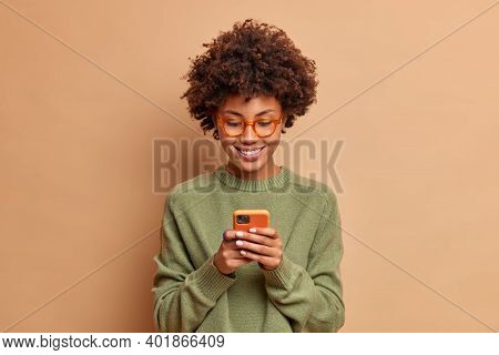 Isolated Shot Of African American Woman Uses Smartphone Application Enjoys Browsing Social Media Cre