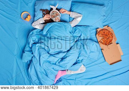 Top View Of Relaxed Young Woman Awakes After Healthy Sleep Stretches Arms Early In Morning Applies C