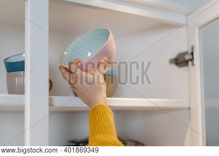 Cropped View Of Woman Standing Near Open Door At Kitchen Cabinet, Puts Clean Ceramic Dishes In The C