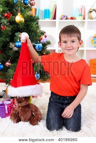 Little boy in Santa hat sits near Christmas tree