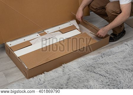 Process Of Unpacking A Box With Furniture.assembly Concept And Purchase Of Furniture .man Collects F