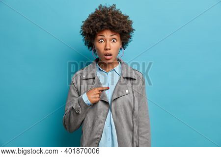 Young Astonished Curly African American Woman Indicates At Herself With Puzzled Expression Shocked T