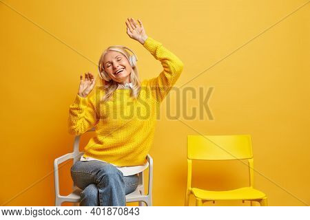 Overjoyed Middle Aged Woman Laughs Out Gladfully Keeps Arms Raised Enjoys Listening Popular Music Vi