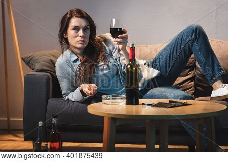 Drunk Woman With Glass Of Red Wine Lying On Sofa Near Bottles Of Alcohol