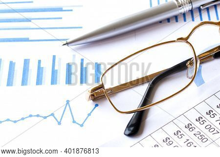 Soft Focus Pen And Eyeglasses On Blur Newspaper Background
