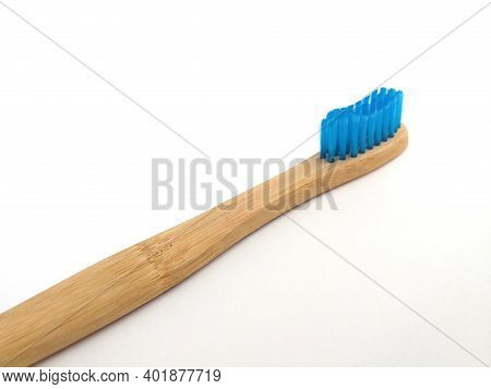 Biodegradable Bamboo Toothbrush Isolated On White Background. Close Up Of Flat Bamboo Brush With Blu