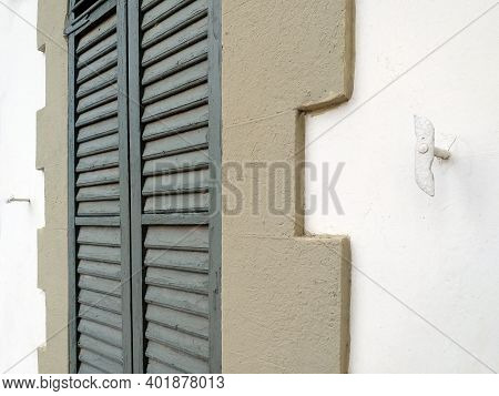 Perspective View Of Closed Green Shutters And Shutter Hooks On White Concrete Wall. Construction Det