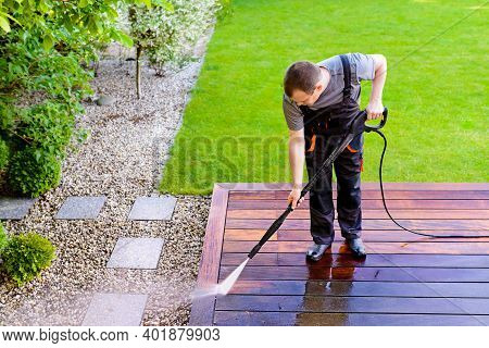 Power Washing - Man Worker Cleaning Terrace With A Power Washer - High Water Pressure Cleaner On Woo