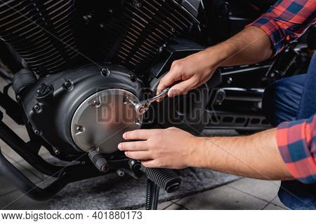 Partial View Of Mechanic Unscrewing Cap Of Motorbike Gearbox With Socket Wrench