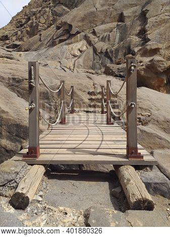 Close Up Of Rustic Wooden Bridge In Arid Ravine With Rock Formations. Hanging Structure Of Old Wood