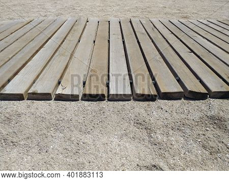 Side View Of Beach Trotter In The Sand On The Beach. Articulated Wooden Walkway Background. Beige Fl