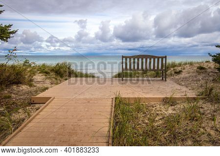The End. Boardwalk Path To An Empty Park Bench Overlooking A Beautiful Lake Horizon On The Coast Of