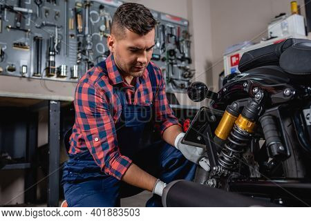 Young Mechanic In Overalls And Plaid Shirt Checking Shock Absorber Of Motorcycle In Workshop