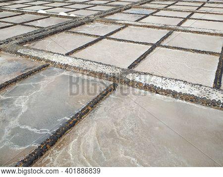 Aerial View Of Salt Evaporation Ponds, Also Called Salterns Or Salt Pans. Natural Salt Flats, Built