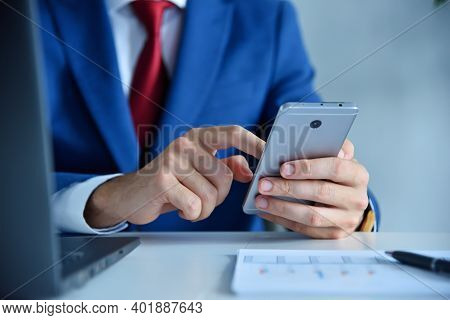 Stock Broker Using Mobile Phone And Checks Report Data. Finance And Trade Concept. Close Up