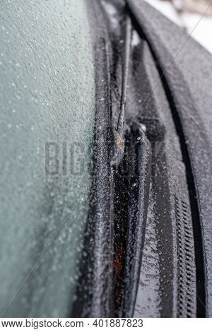 Closeup Of Wipers And Frosted Car Windshield Covered With Ice At Shallow Depth Of Field