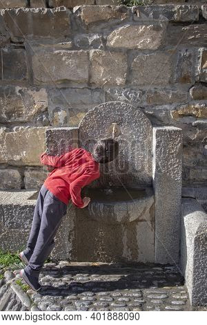 Child On His Back Drinks Water On Tiptoe In A Stone Fountain In Ainsa, Huesca Spain, Vertical