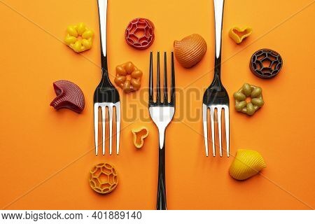 Three Forks With Some Types Of Colored Pasta On An Orange Surface