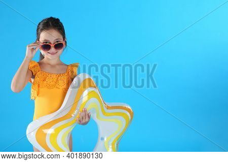 Cute Little Child In Beachwear With Inflatable Ring On Light Blue Background. Space For Text