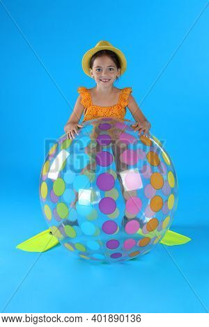 Cute Little Child In Beachwear With Inflatable Ball On Light Blue Background