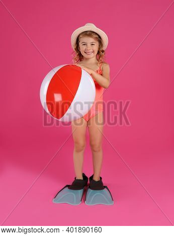 Cute Little Child In Beachwear With Bright Inflatable Ball On Pink Background