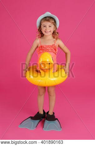 Cute Little Child In Beachwear With Bright Inflatable Ring On Pink Background
