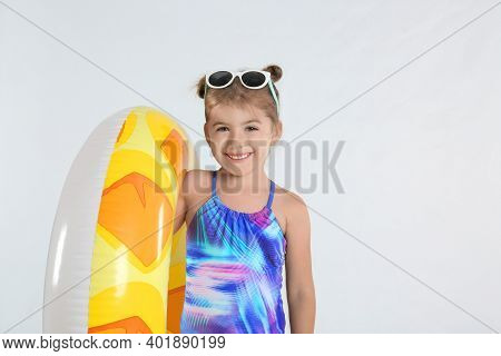 Cute Little Child In Beachwear With Bright Inflatable Ring On White Background