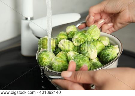 Woman Washing Brussels Sprouts With Running Water Over Sink, Closeup