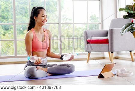 Asian Woman Hand Holding Bottle Of Water As Dumbbell While Online Exercise At Home, Female Lifting S