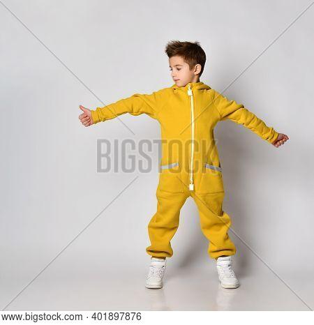 Studio Portrait Shot Of Little Boy In Yellow Fleece Sportswear Showing Thumbs-up And Looking Aside S