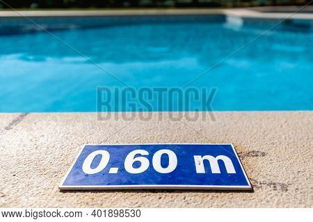 Blue Plastic Plate At The Edge Of A Swimming Pool Indicating A Depth Of 0.60 Meters