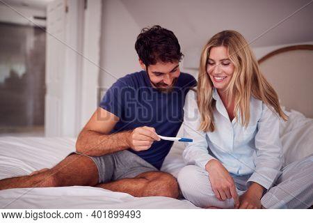 Excited Couple Wearing Pyjamas In Bedroom Celebrating Positive Pregnancy Test
