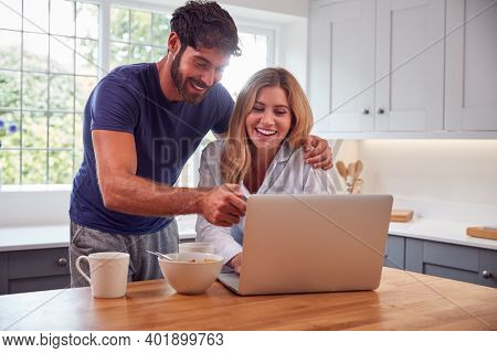 Couple Wearing Pyjamas In Kitchen Watching Laptop Whilst Eating Breakfast