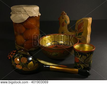Glass Jar Of Preserved Tomato, A Spoon With Folk Painting And A Wooden Bowl