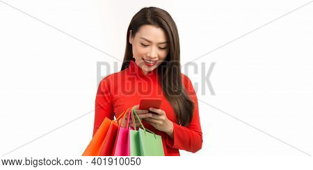 Asian Woman Wearing Ao Dai Dress Use Smart Phone And Do The Shopping With Some Bags On Her Hand