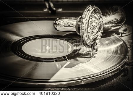 Old Gramophone Plays An Old Vinyl Record. Old Style Black And White Photo In Sepia.