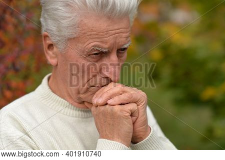 Close Up Portrait Of Thoughtful Senior Man Outdoors