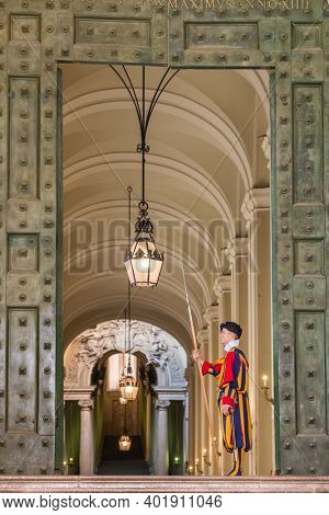 Vatican - June 1, 2020: Unidentified Papal Swiss guard standing at the Vatican Museums door in the Vatican. The Swiss guards served since the late 15th century.