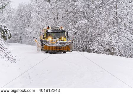 A Snow Blower Car Clears Snow In The Forest From The Road On A Winter Morning. Snow Plow Truck Clean