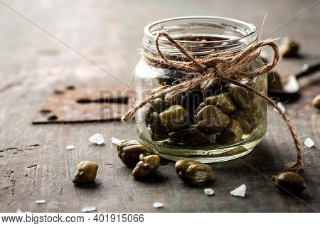 Capers Marinated Capers In A Jar On Wooden Background. Place For Text. Delicious Ingredients For Coo
