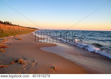 Golden Sunset On A Wide Sandy Beach Along The Coast Of Lake Michigan As Waves Crash Onto The Shore.