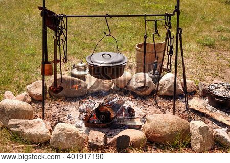 Cooking Over A Campfire. Large Kettle Simmering Over A Hot Bed Of Coals From A Campfire.