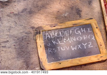 Home Schooling. Hand Held Chalkboard With Alphabet Written In Chalk. Horizontal Orientation With Cop