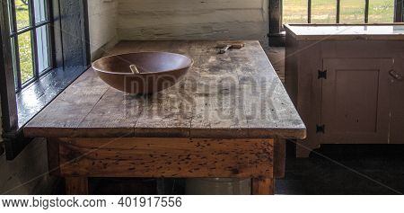 Simple Rural Farmhouse Kitchen With Wooden Table And Bowl In Vertical Orientation. This Is A Histori