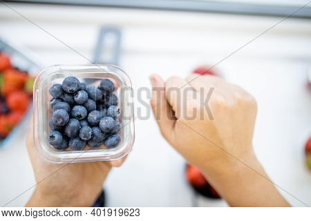 Female Fist Next To Small Plastic Container Full Of Blueberries Above Blurry Fruit. Fresh And Blurry